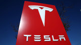 Tesla posts rare profit, stock pops 6%